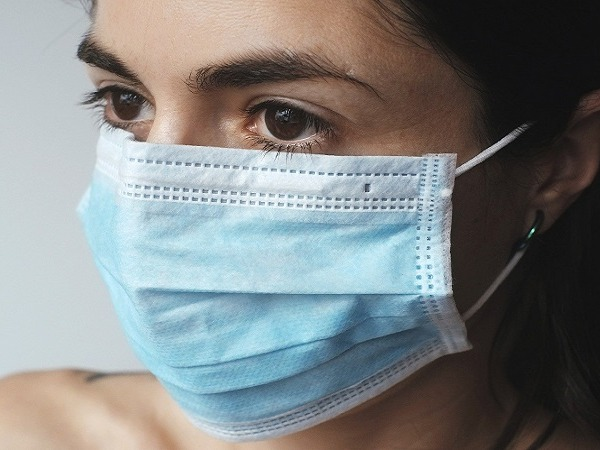 A head shot of a young woman wearing a disposable facemask