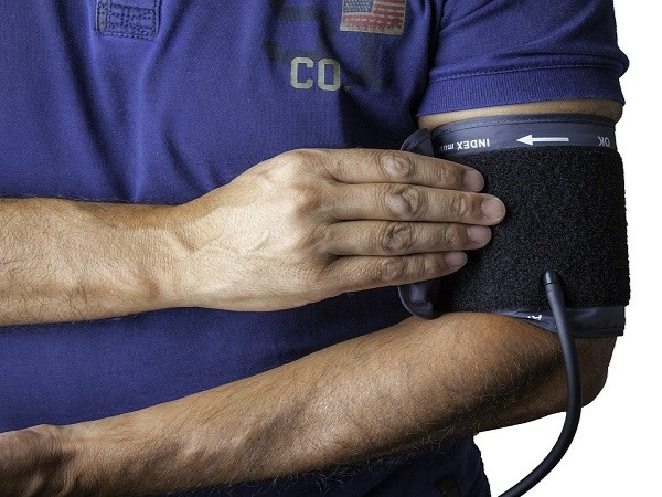 A man in a polo shirt fixing a blood pressure monitor to his upper arm on a white background