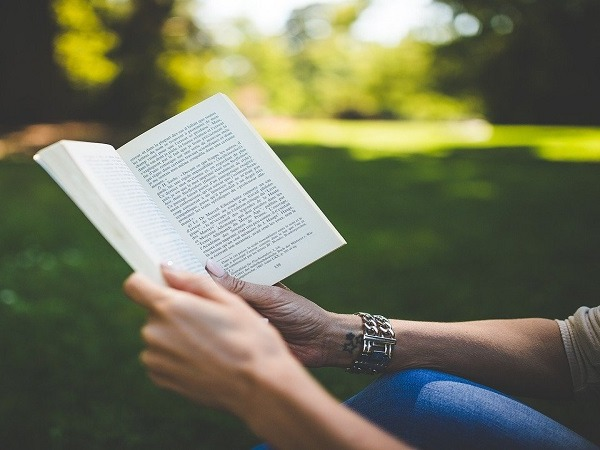 A couple holding a book open between them in a park
