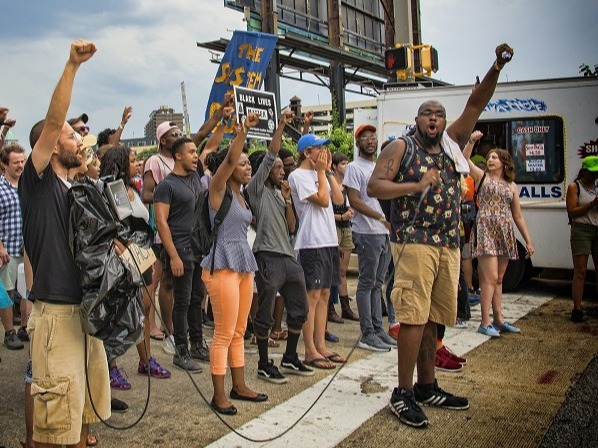 A group of raise their fists at a Black Lives Matter protest