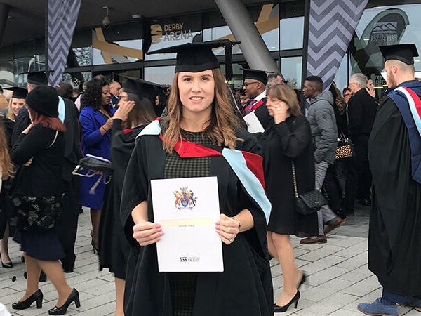 Weronika outside at graduation in her gown and cap holding her postgraduate certificate
