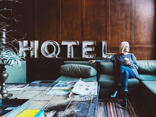 A woman sitting on a settee in a wood panelled hotel lobby with a takeaway drinks holder. The word 'Hotel' is written behind her in large metal letters.