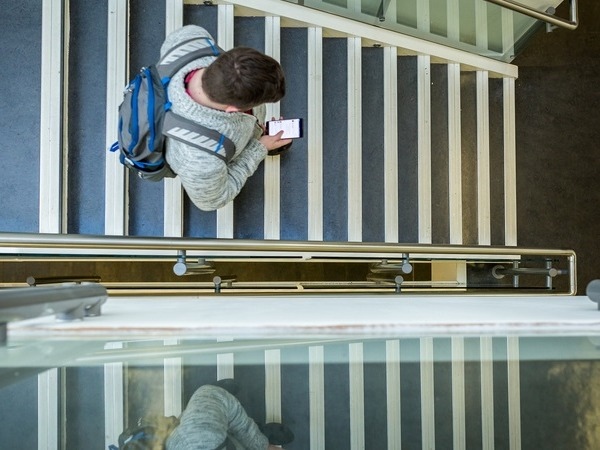 Top down view of a student walking down stairs while looking at his phone