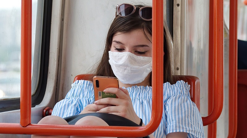 Person wearing a face mask on their phone