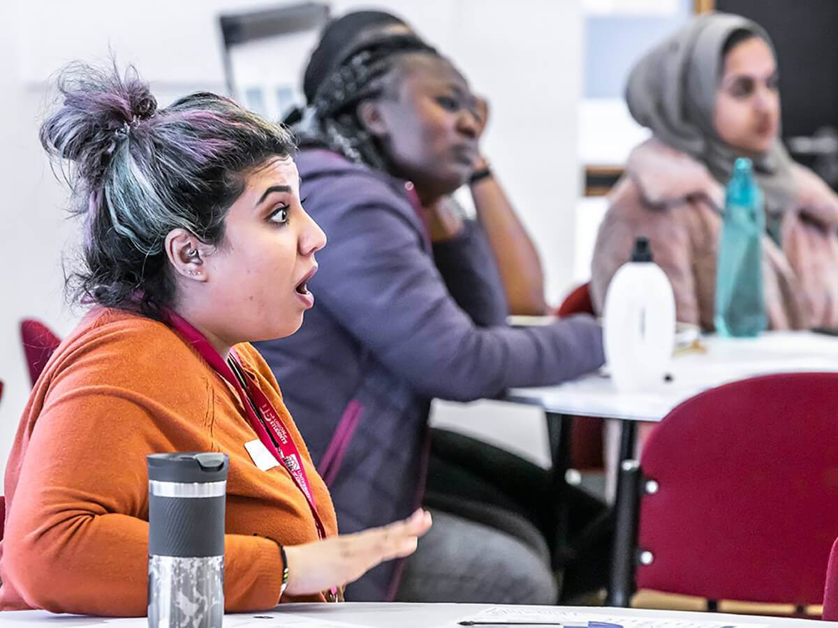 A young woman speaking passionately at a conference