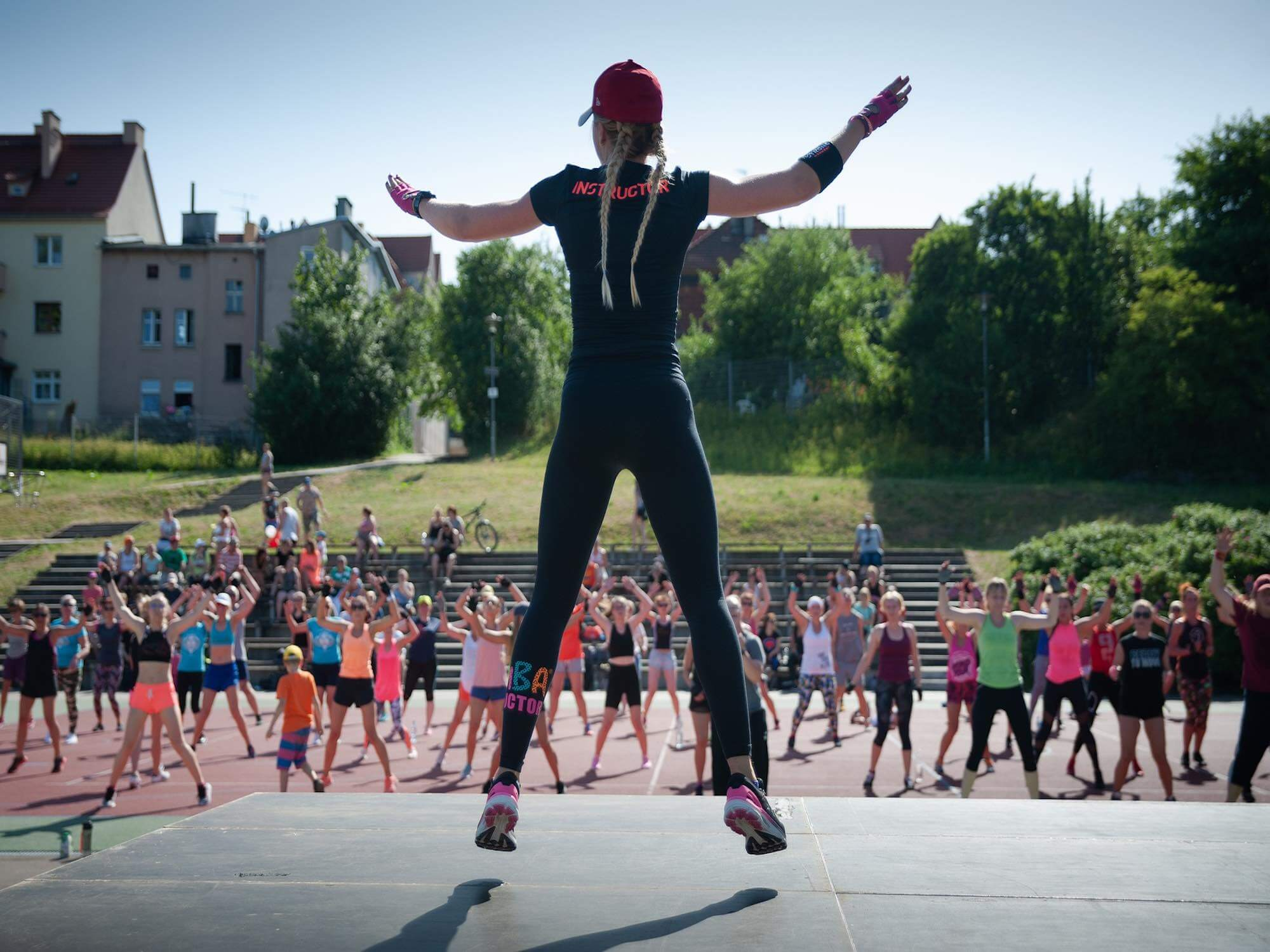 A dance instructor leads a large outdoor class