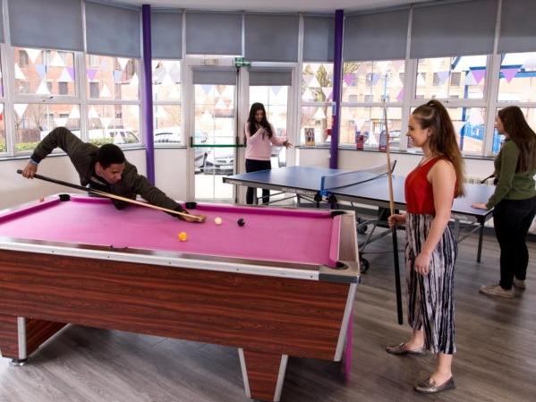 Students playing pool and table tennis in a halls common area