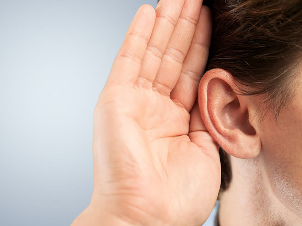 Person with hand cupped to ear to aid hearing