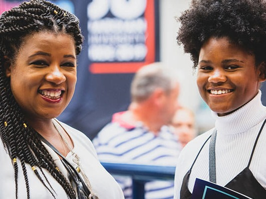 Two smiling women at an event in the University of Derby atrium