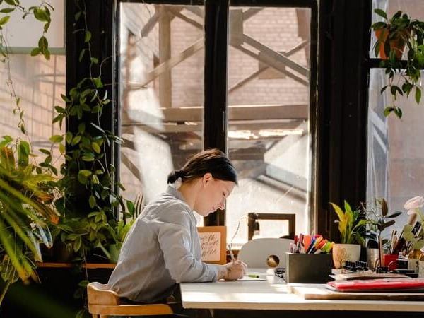 A young woman concentrating while on a tablet at a desk by a large window