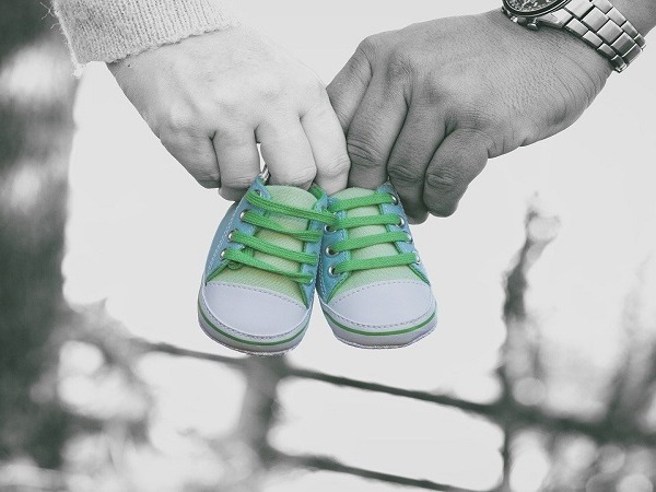 Male and female hands holding a pair of baby shoes between them