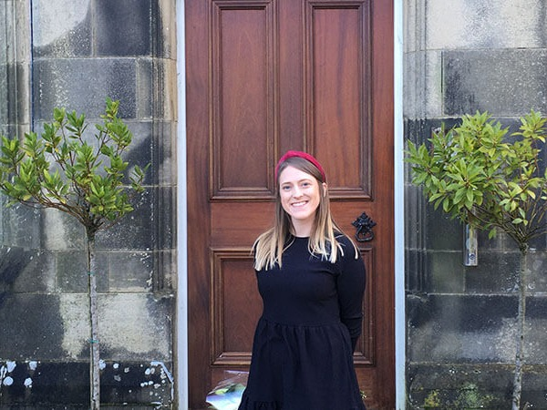 Laura Stroud standing in front of a wooden front door with potted bushes either side