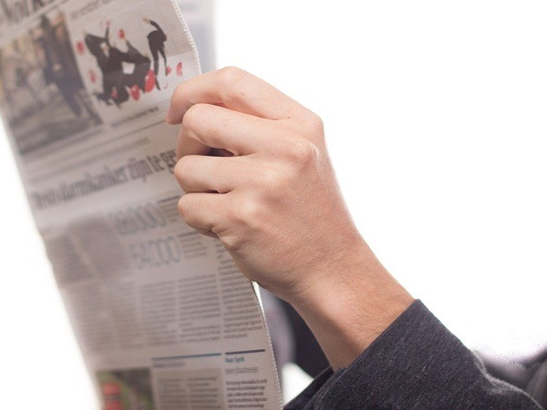 A pair of arms holding a newspaper shot on a white background
