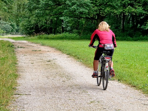 A woman riding a bike down a gravel path in a wooded area