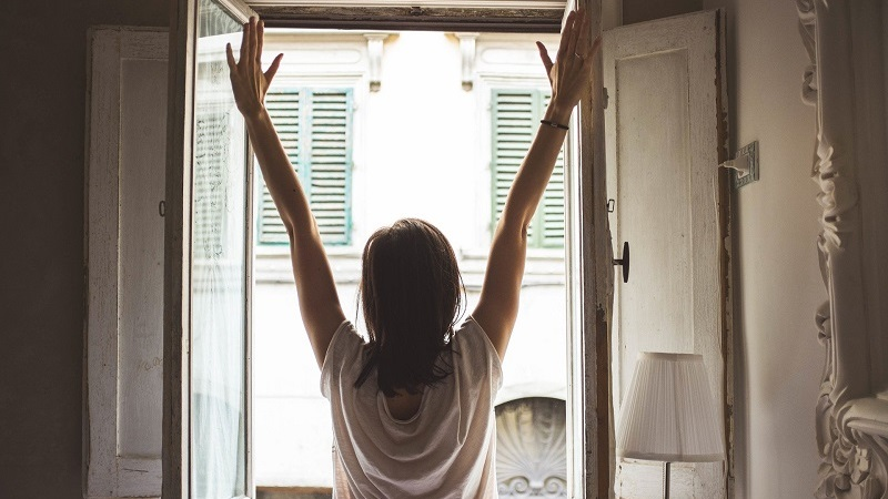 A woman stretching in front of a window
