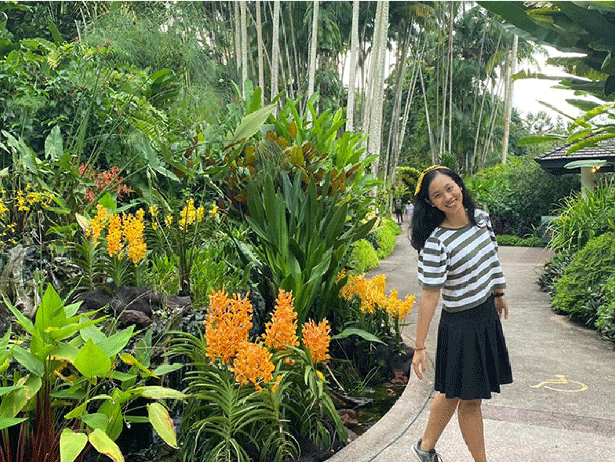 Huyen standing in a garden, smiling.