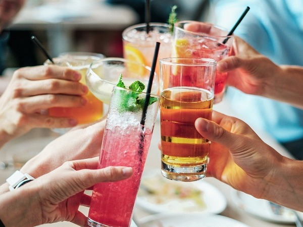 A group of people clinking drinks over a table