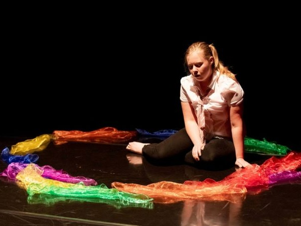 A University of Derby arts therapy student sitting on a theatre floor surrounded by coloured silk scarves