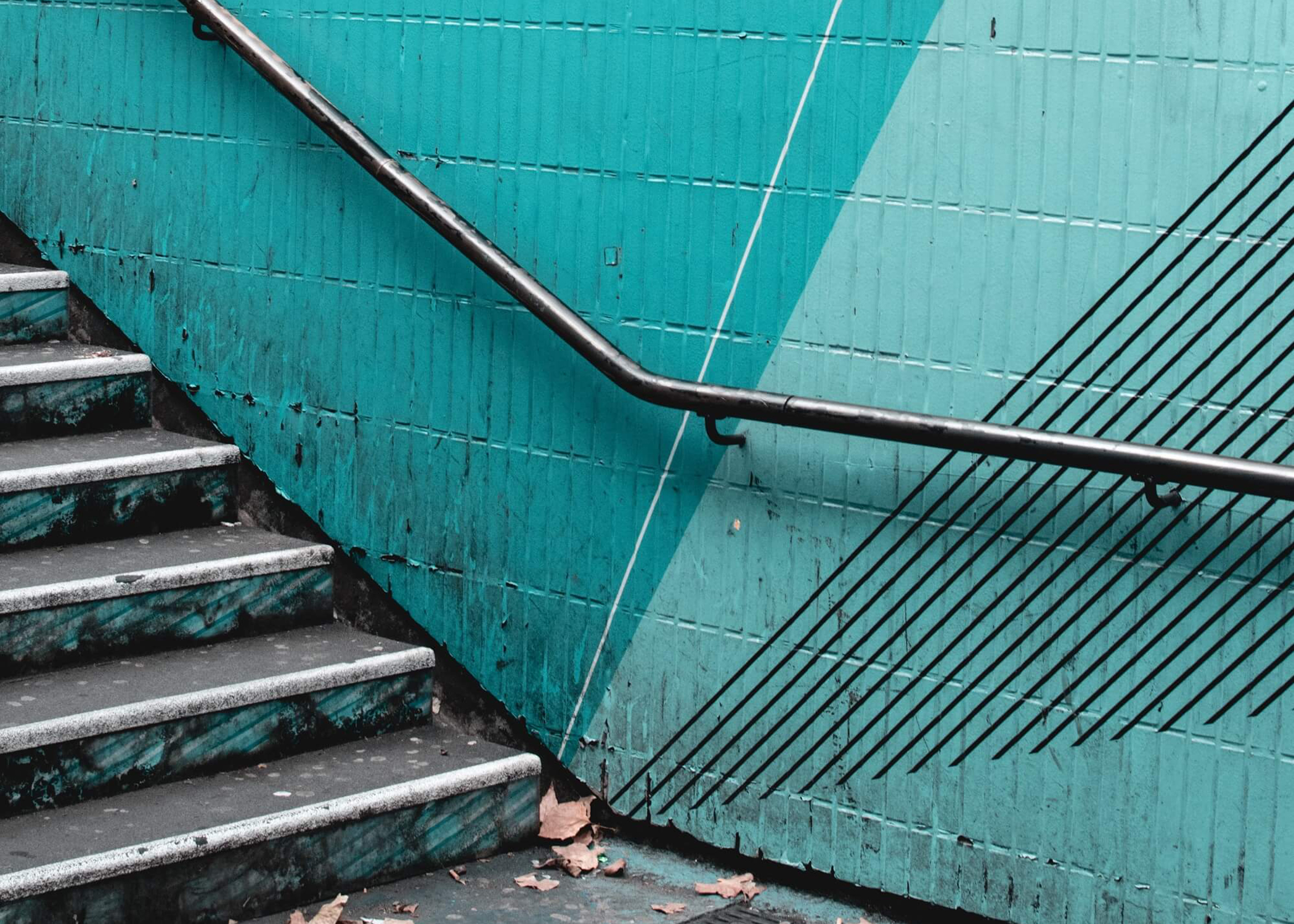 Dilapidated stairway leading up from a subway tunnel, painted turquoise.