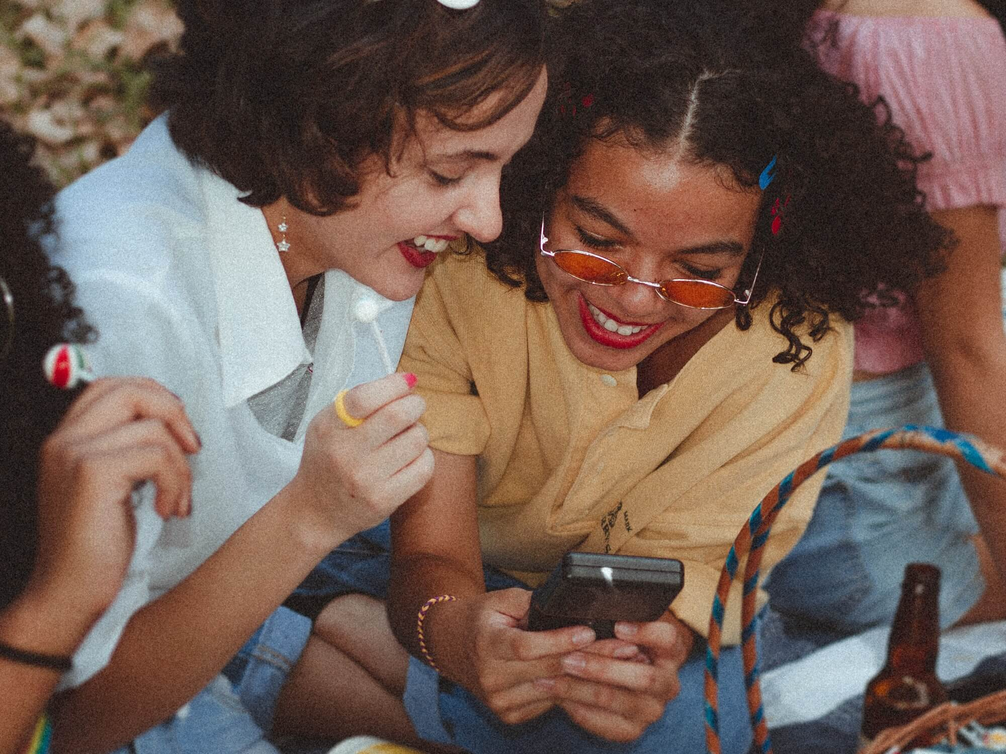 Group of friends at a picnic, two people are looking at a phone screen and smiling.