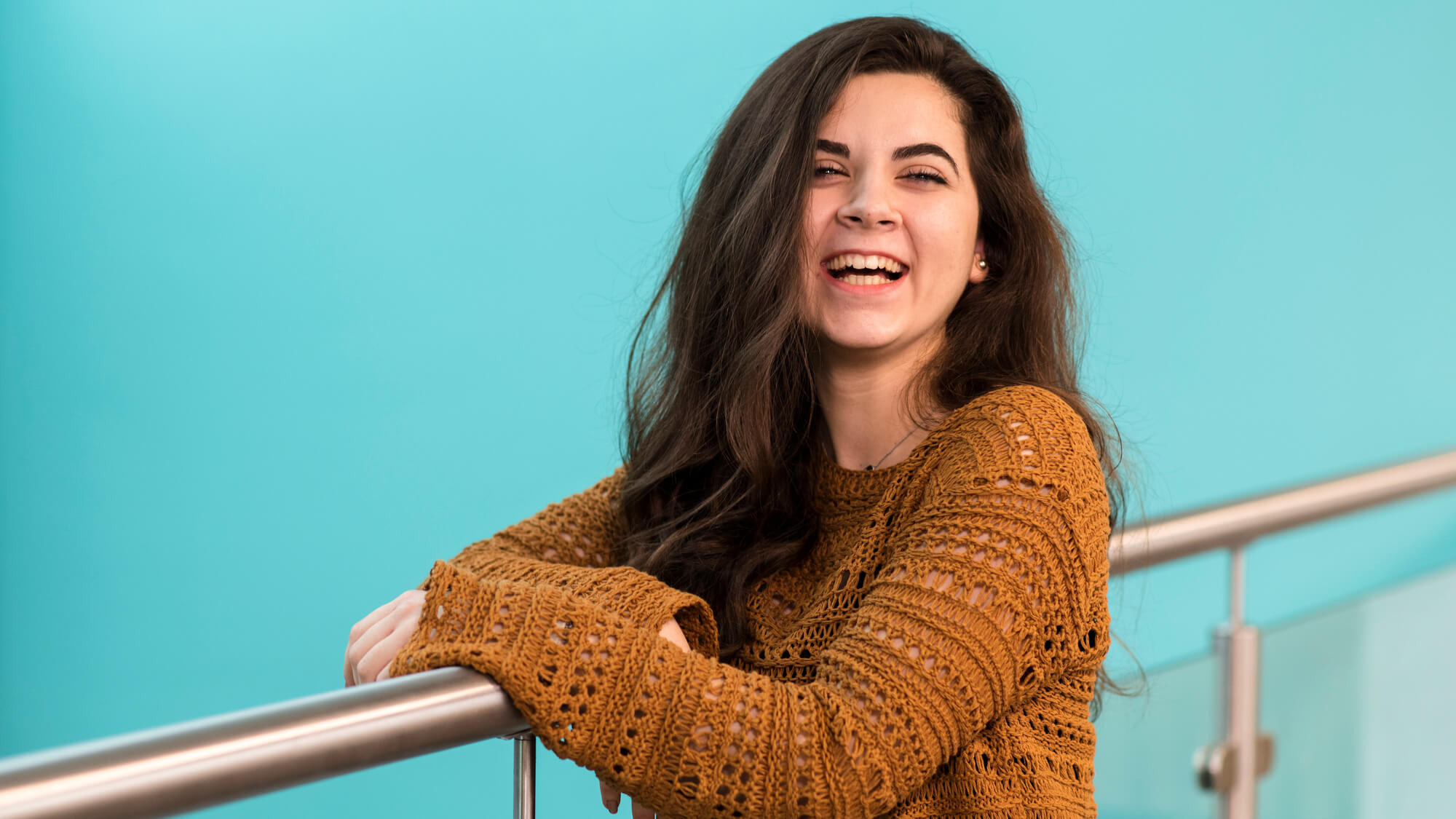A dark haired female student leans on a wall smiling and laughing