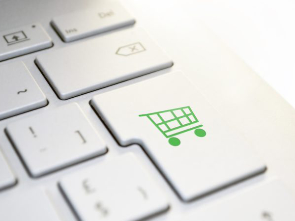 White Apple keyboard with a green shopping trolley icon on the 'return' key