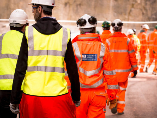 Workers walking at a quarry site wearing high-vis clothing and hard hats