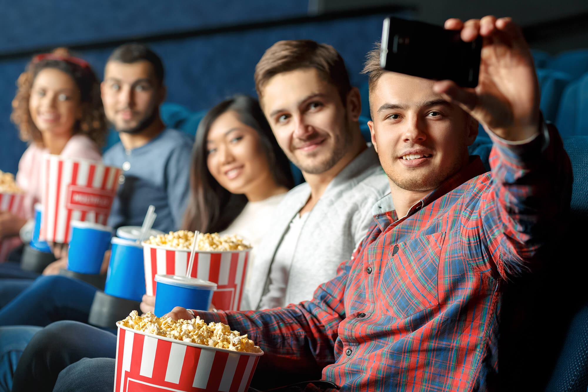 A group take a selfie in a cinema screen