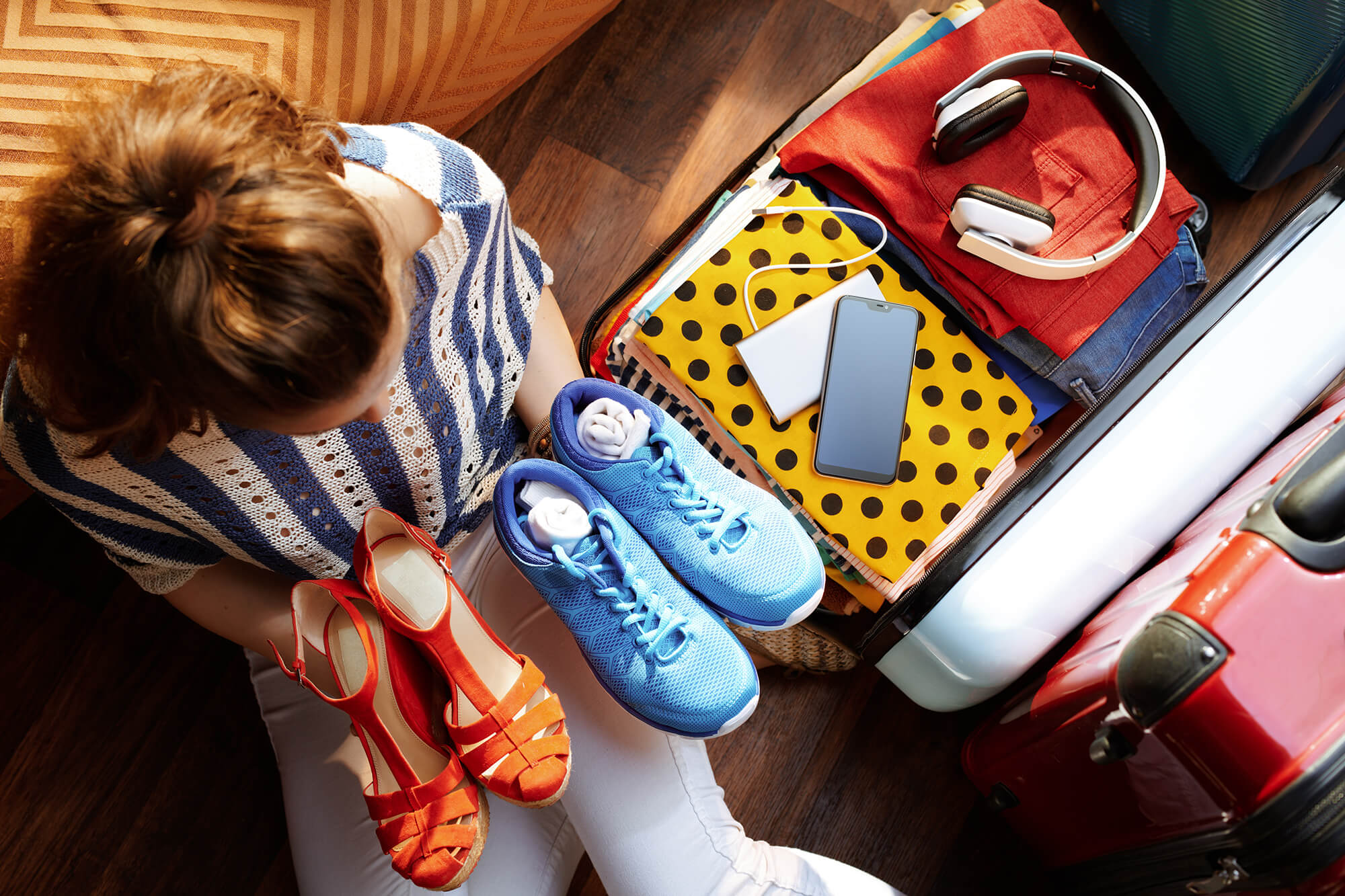 A person holds a pair of trainers in one hand and a pair of orange sandals in another. They are sitting on their bed, next to a suitcase which contains headphones, folders and a mobile phone.