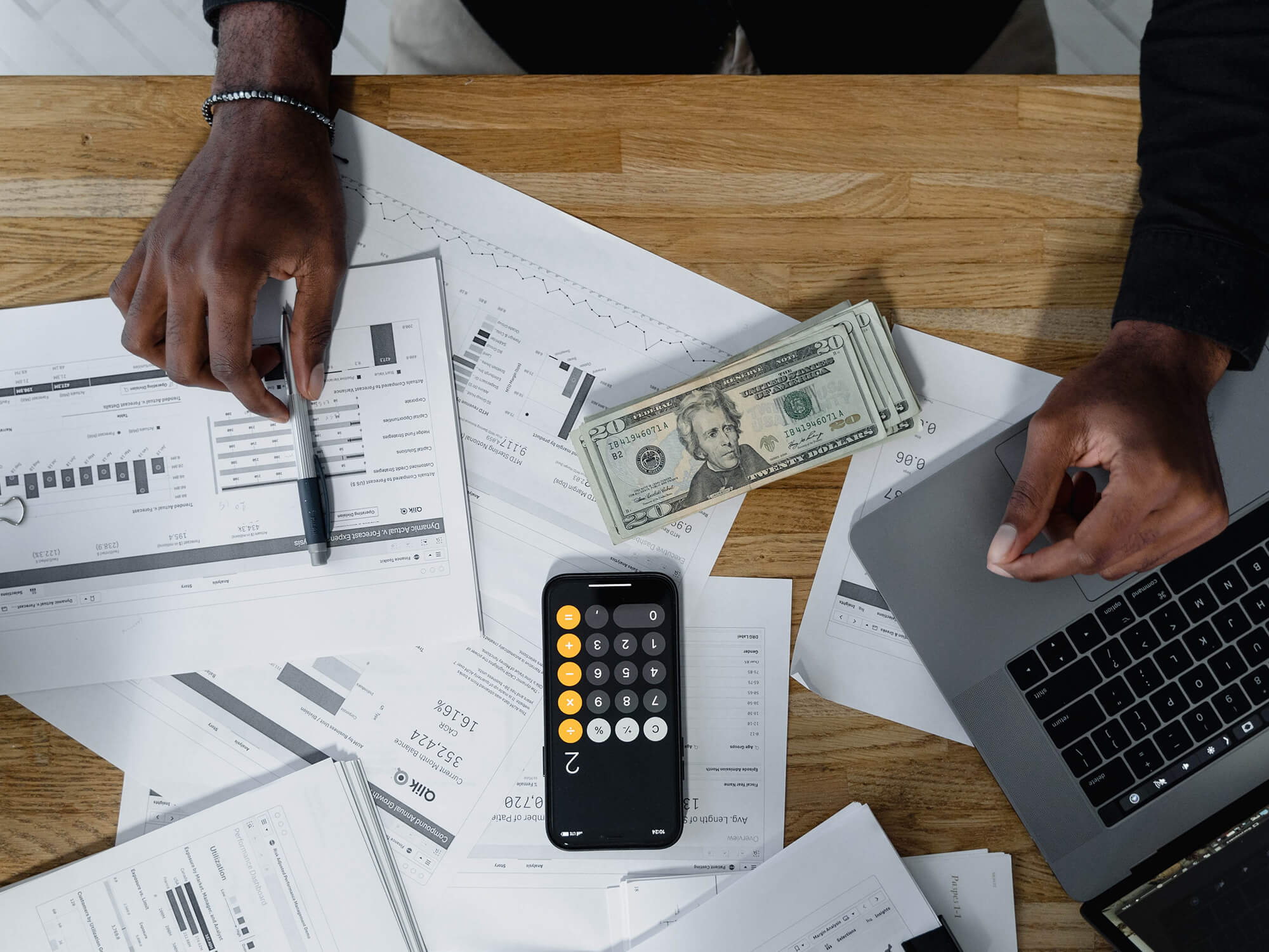 Paperwork, a calculator and money placed on a wooden table with a laptop