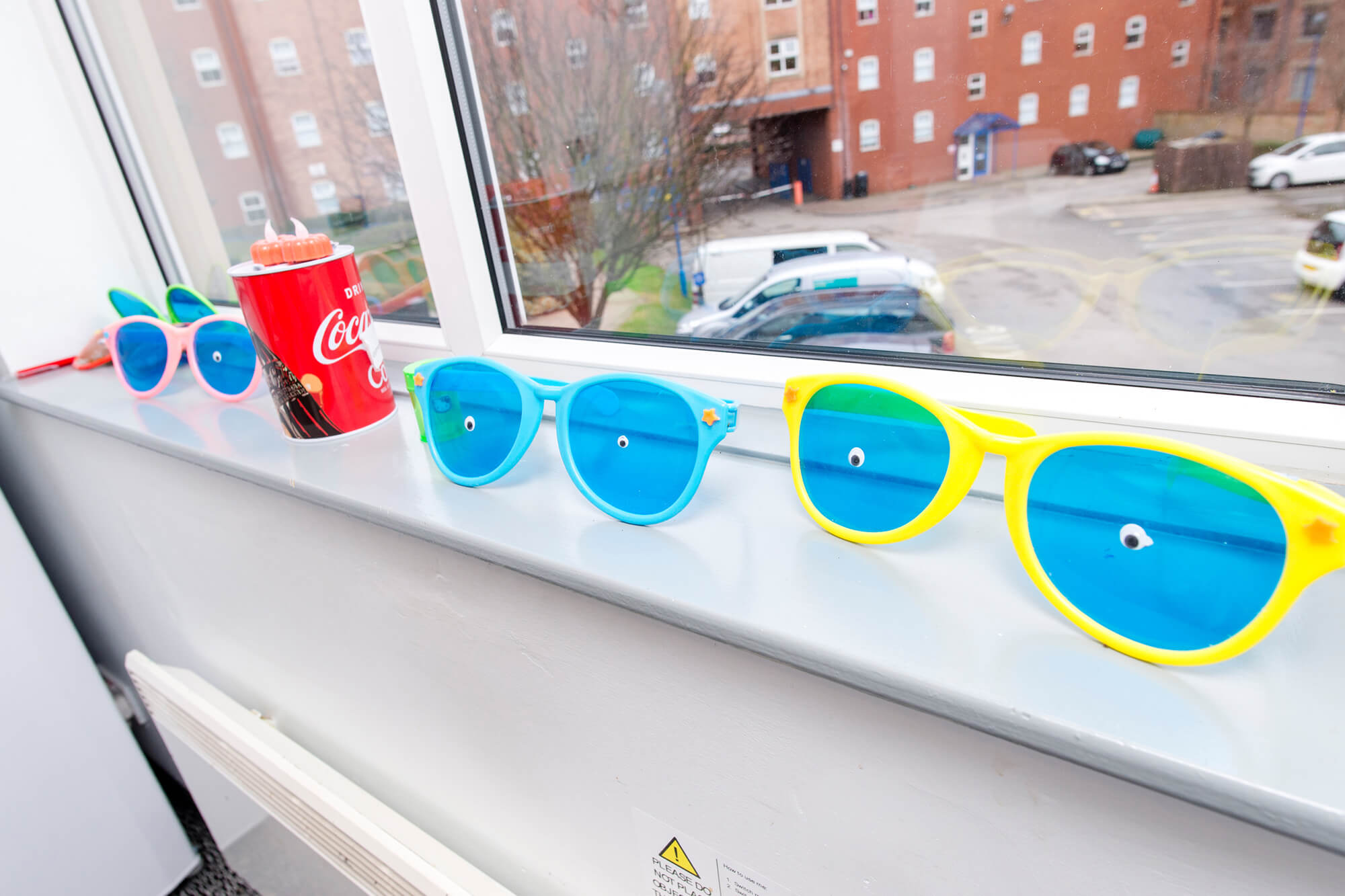 Plastic sunglasses with novelty eyes lined against a windowsill in student halls of residence.