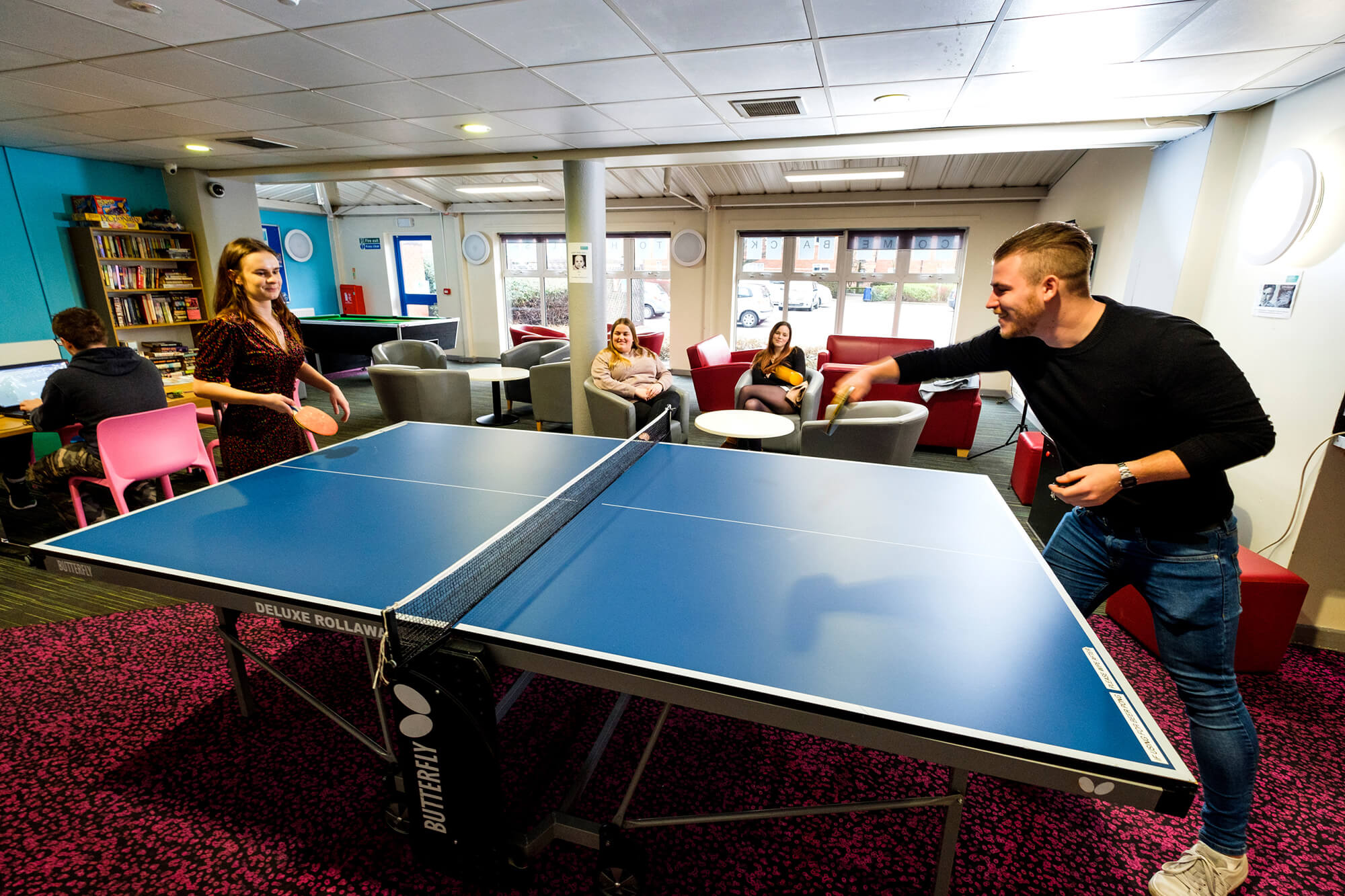 Students playing table tennis in halls