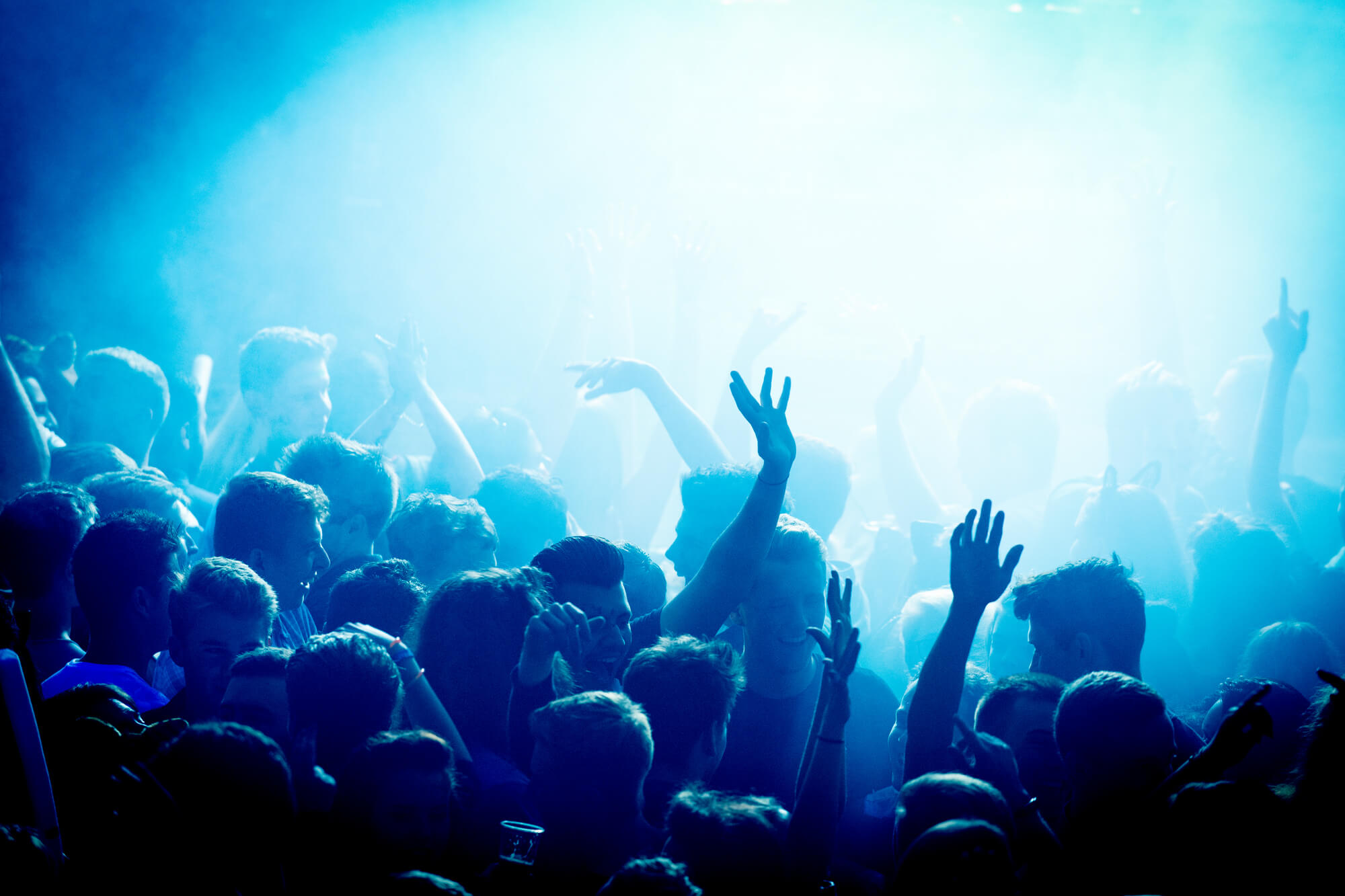 Freshers' party. People holding their hands up in the air under blue lighting.