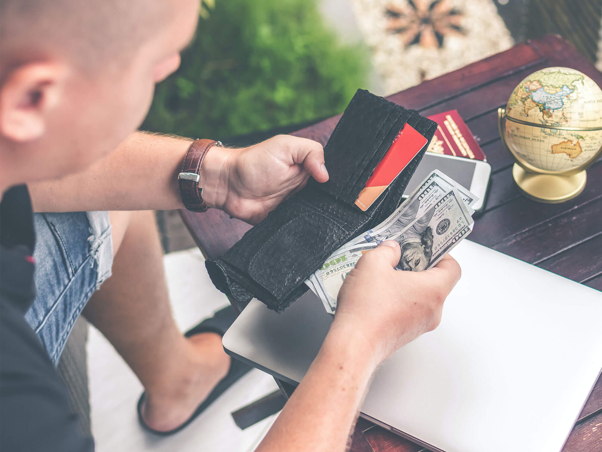 Man sits looking at money in his wallet