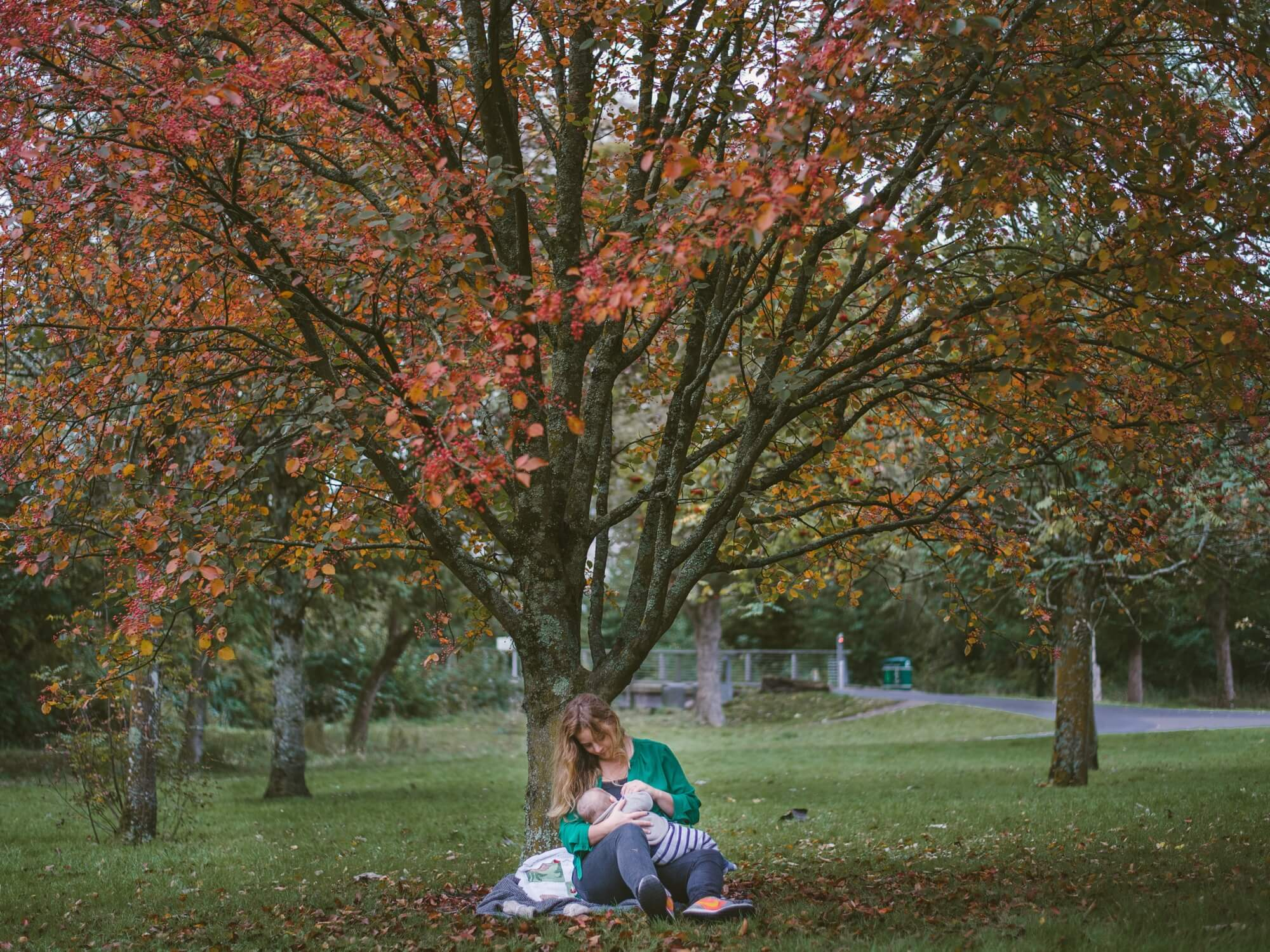 A woman sitting under a tree in a park, holding a baby in her lap