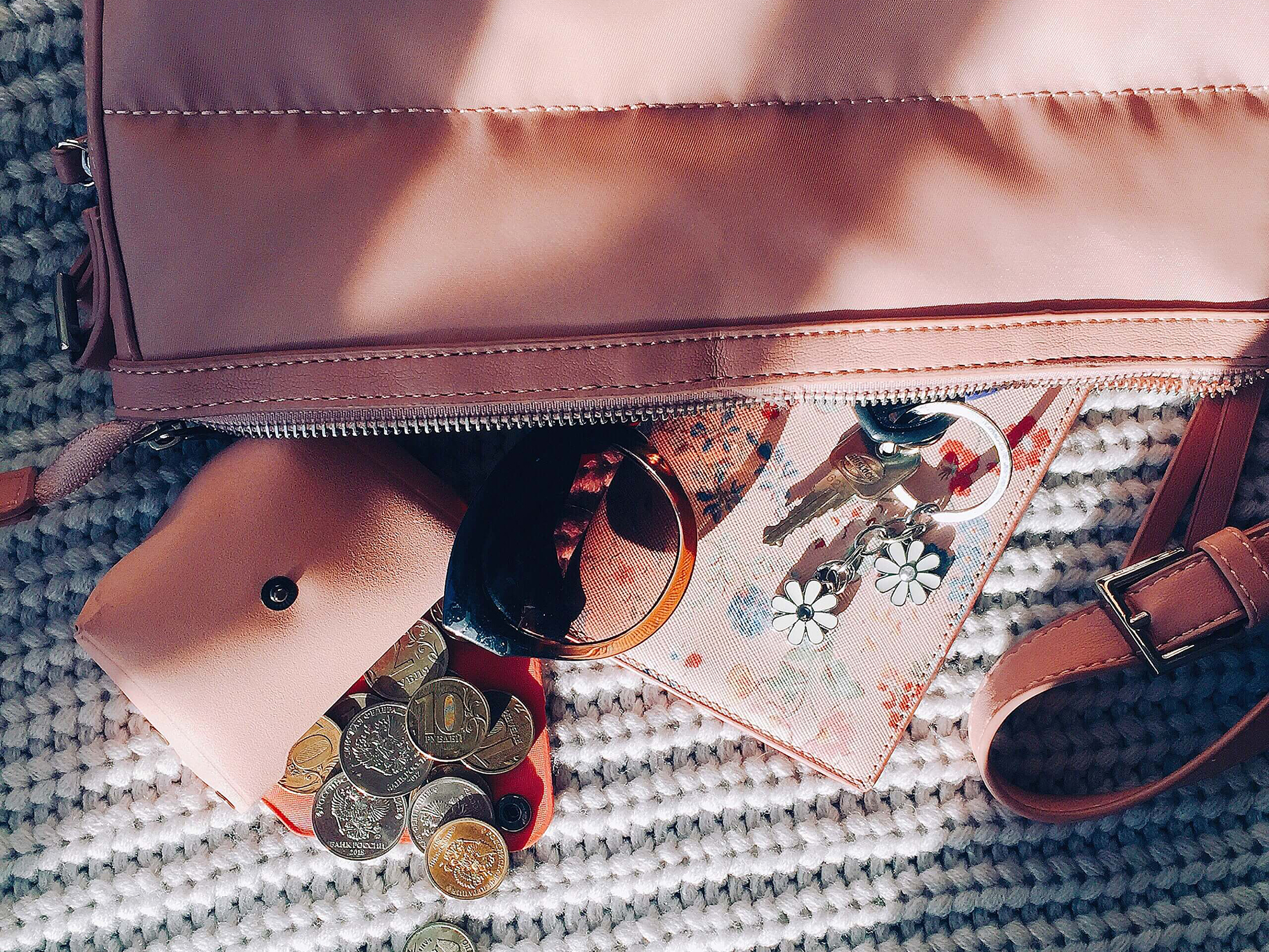 Pink handbag and wallet, coins are laid out next to a coin purse.