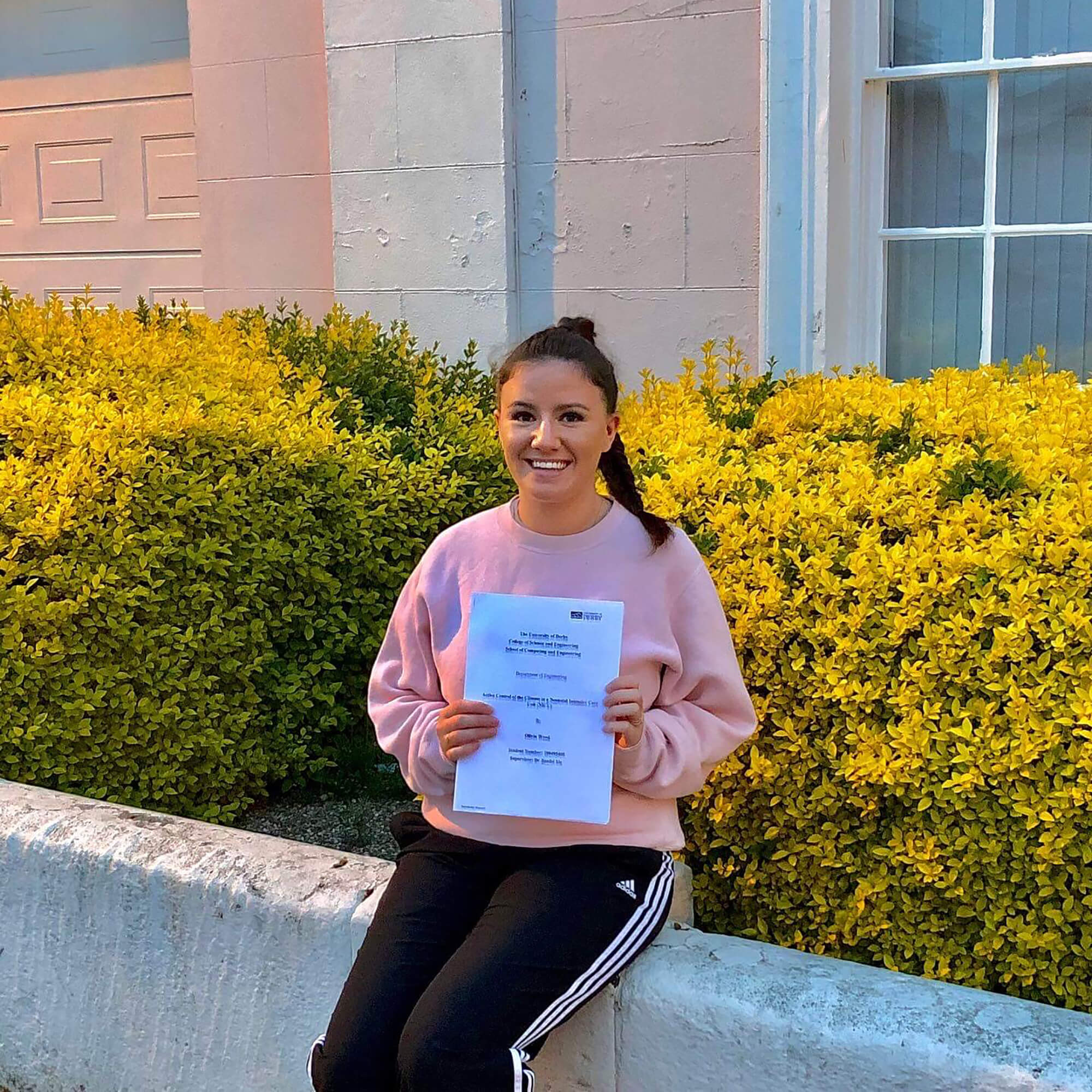 Student Olivia Wood holding her dissertation