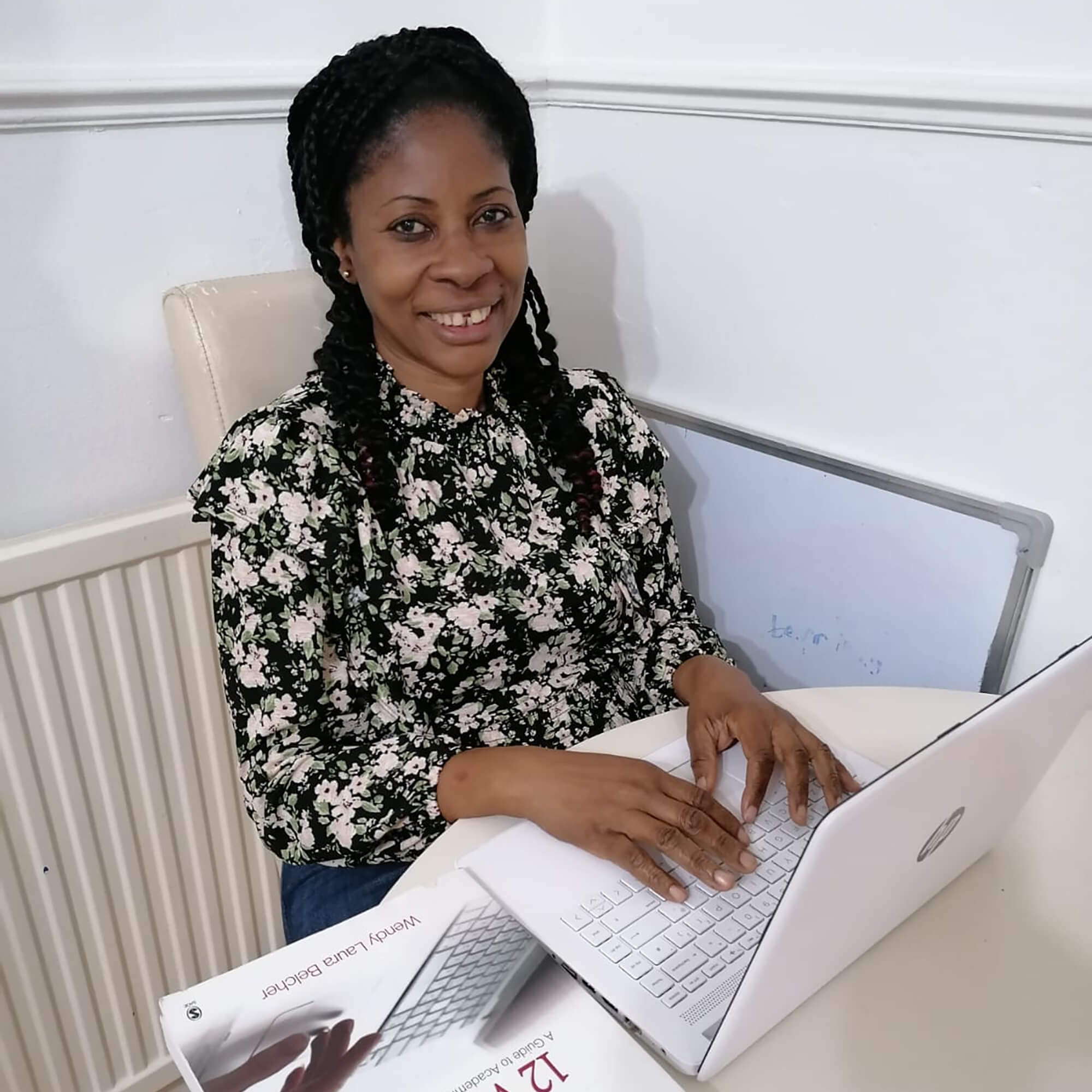 Adetutu sitting a a desk typing on a laptop.