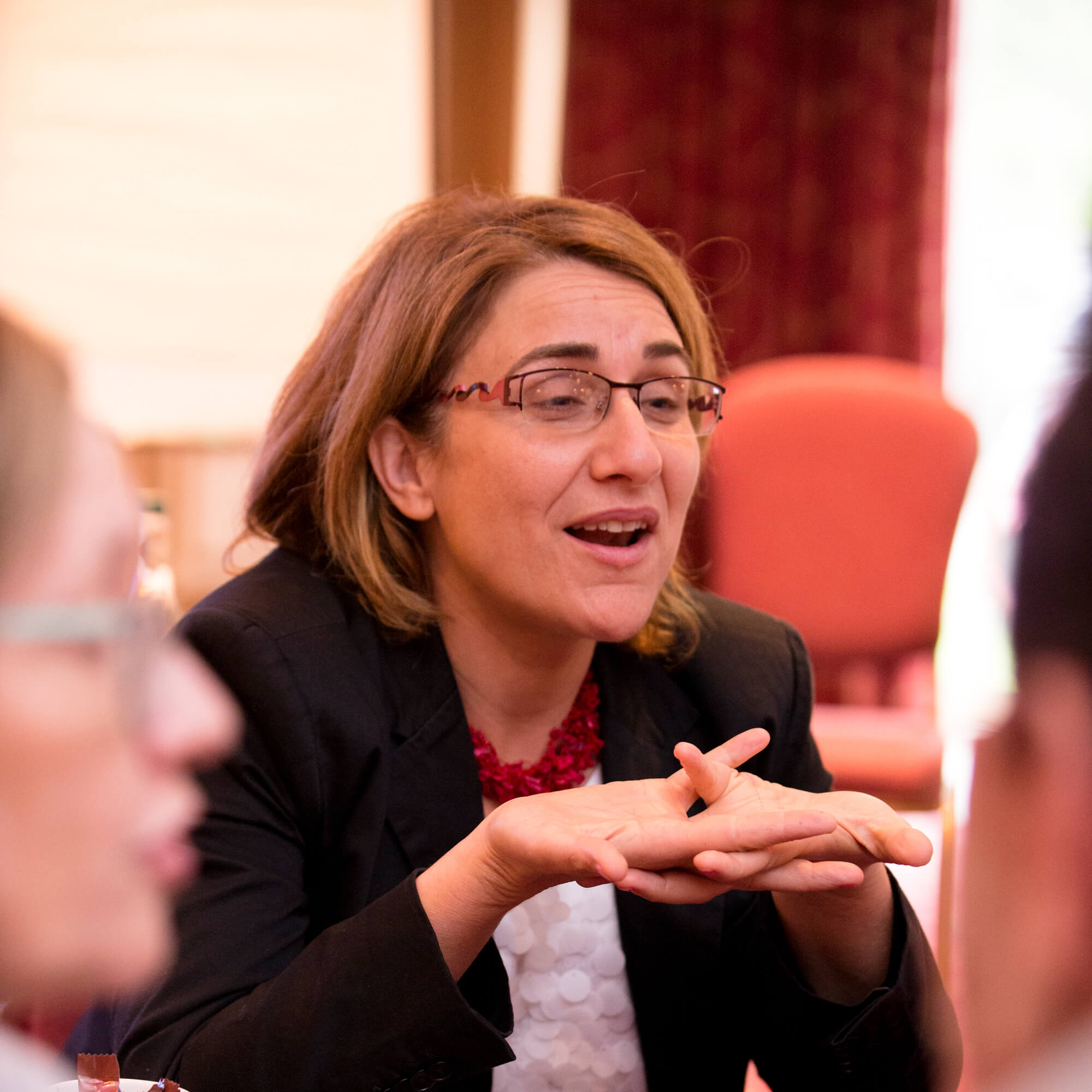Woman with light brown hair and glasses sitting at a table holding a discussion