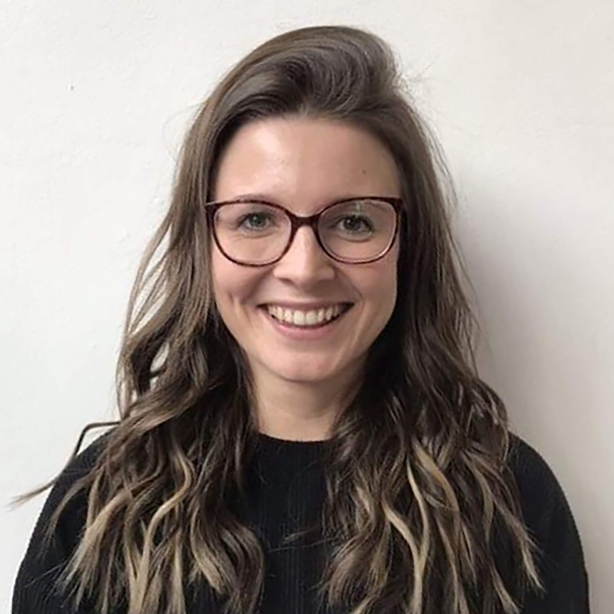 Beth Collinson smiling wearing glasses