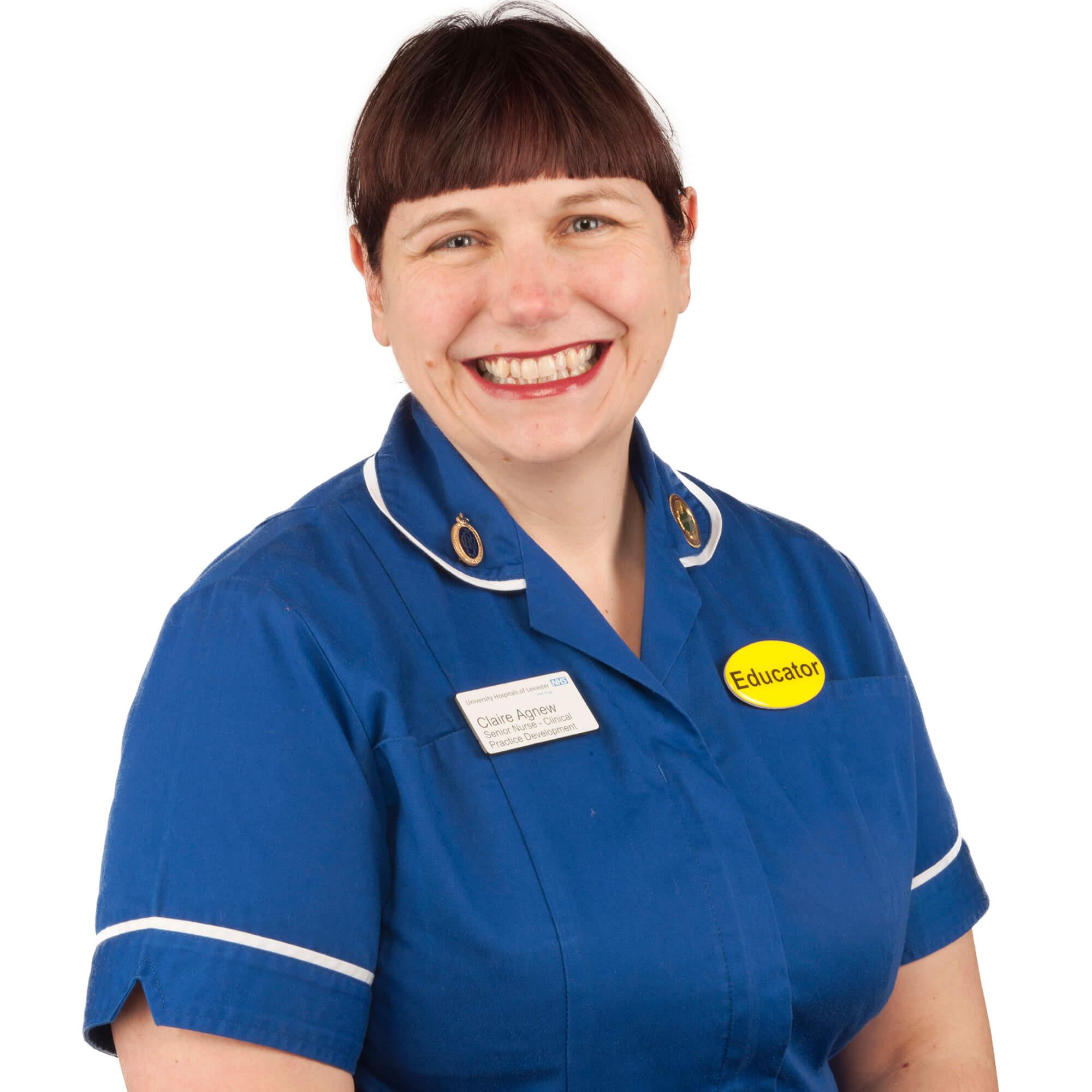 Claire wearing a nurse's uniform sitting, smiling.