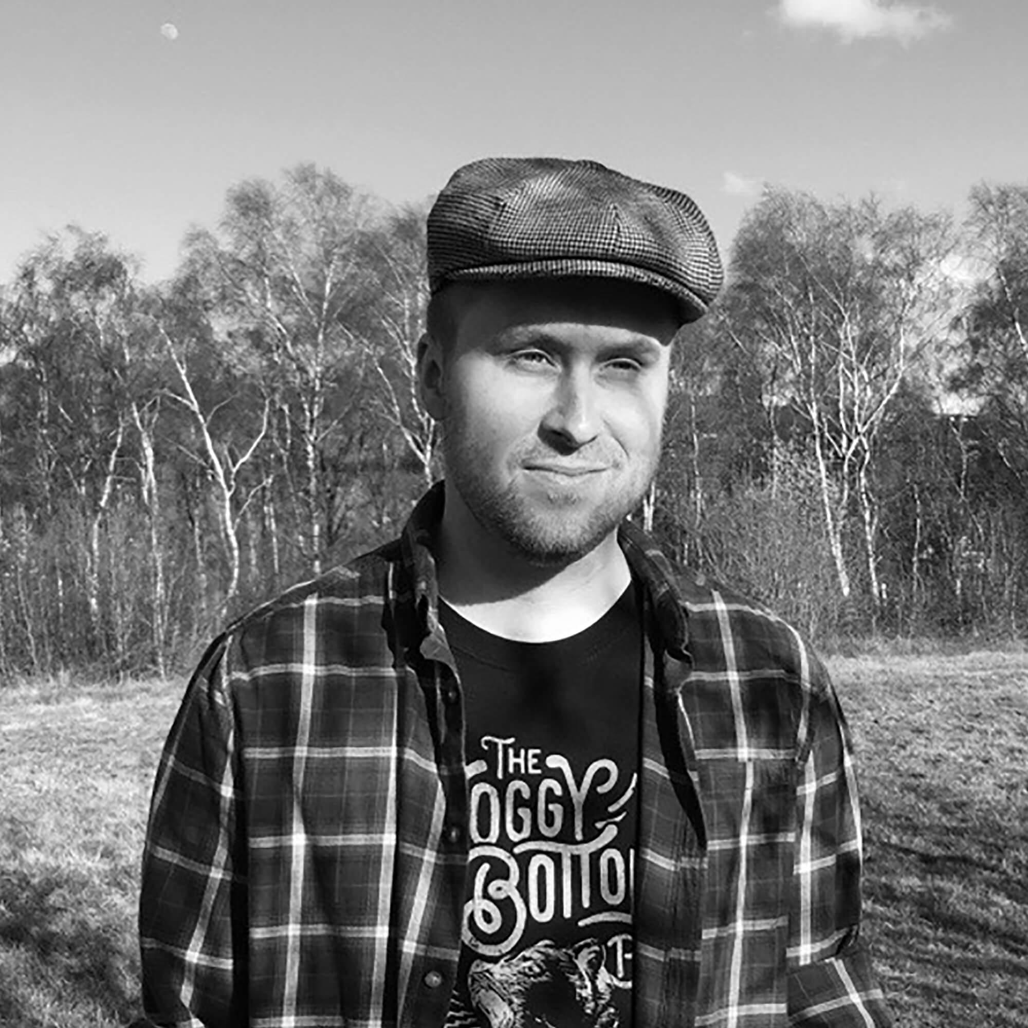 Daniel wearing a flat cap standing outside amongst trees.