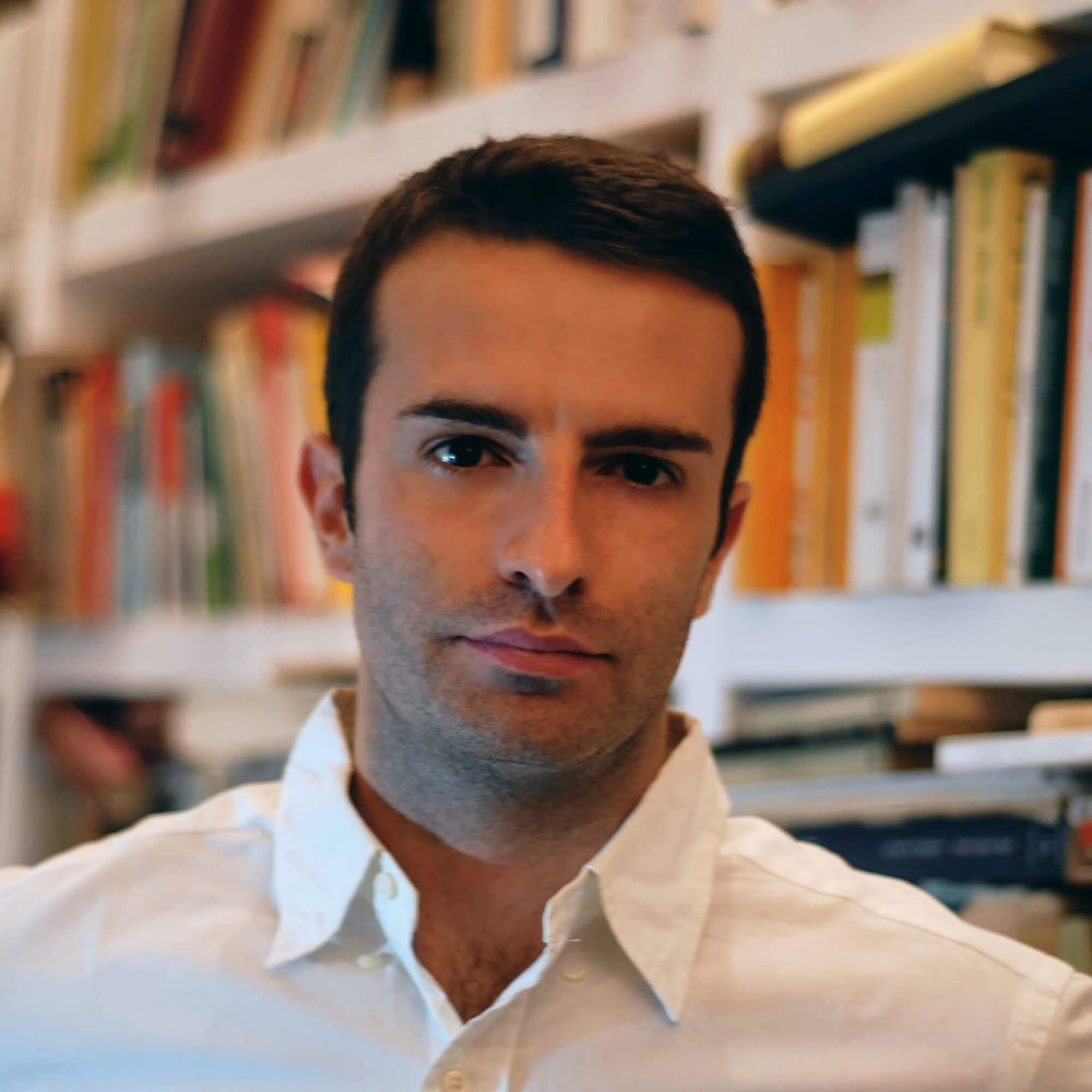 Francesco wearing a white shirt, standing in front of a bookcase.