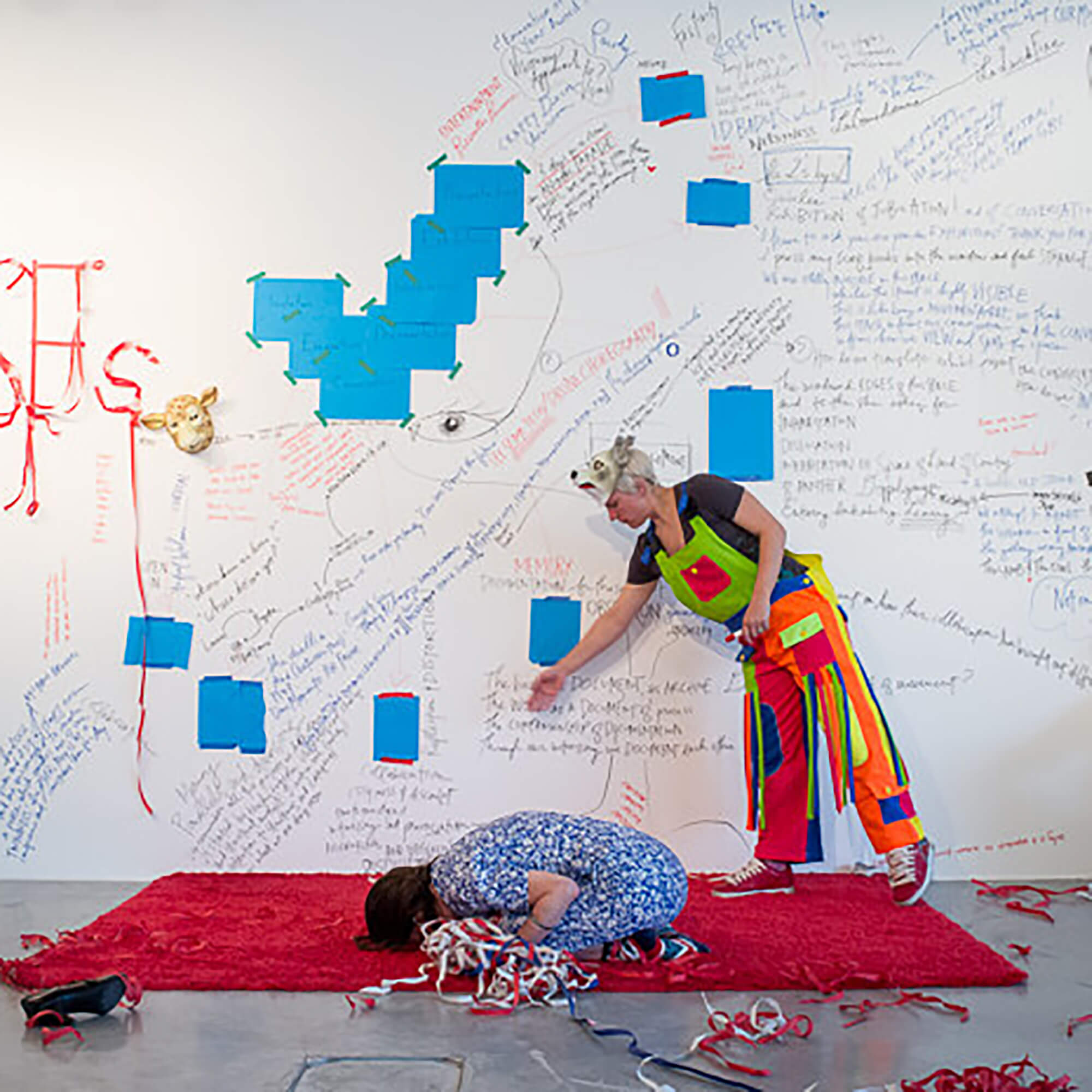 'Amiga' Performance. Person crouching on the floor on a red mat. Another person stands nearby pointing to a wall containing written messages and drawings.