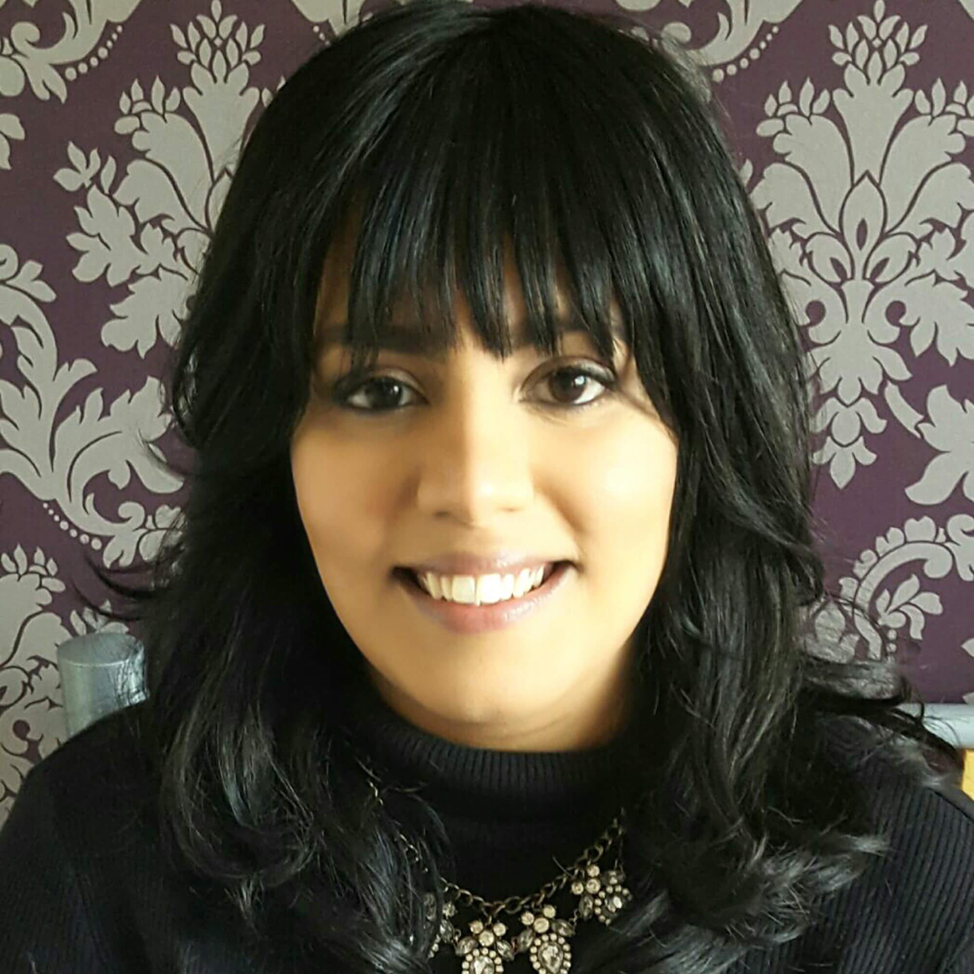 Jaskaran wearing a black top, smiling.
