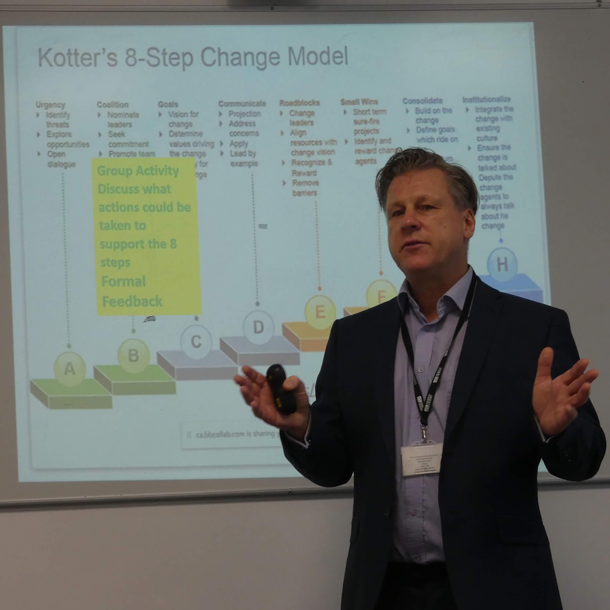 John giving a presentation. A slide behind him refers to Kotter's 8 step Change Model