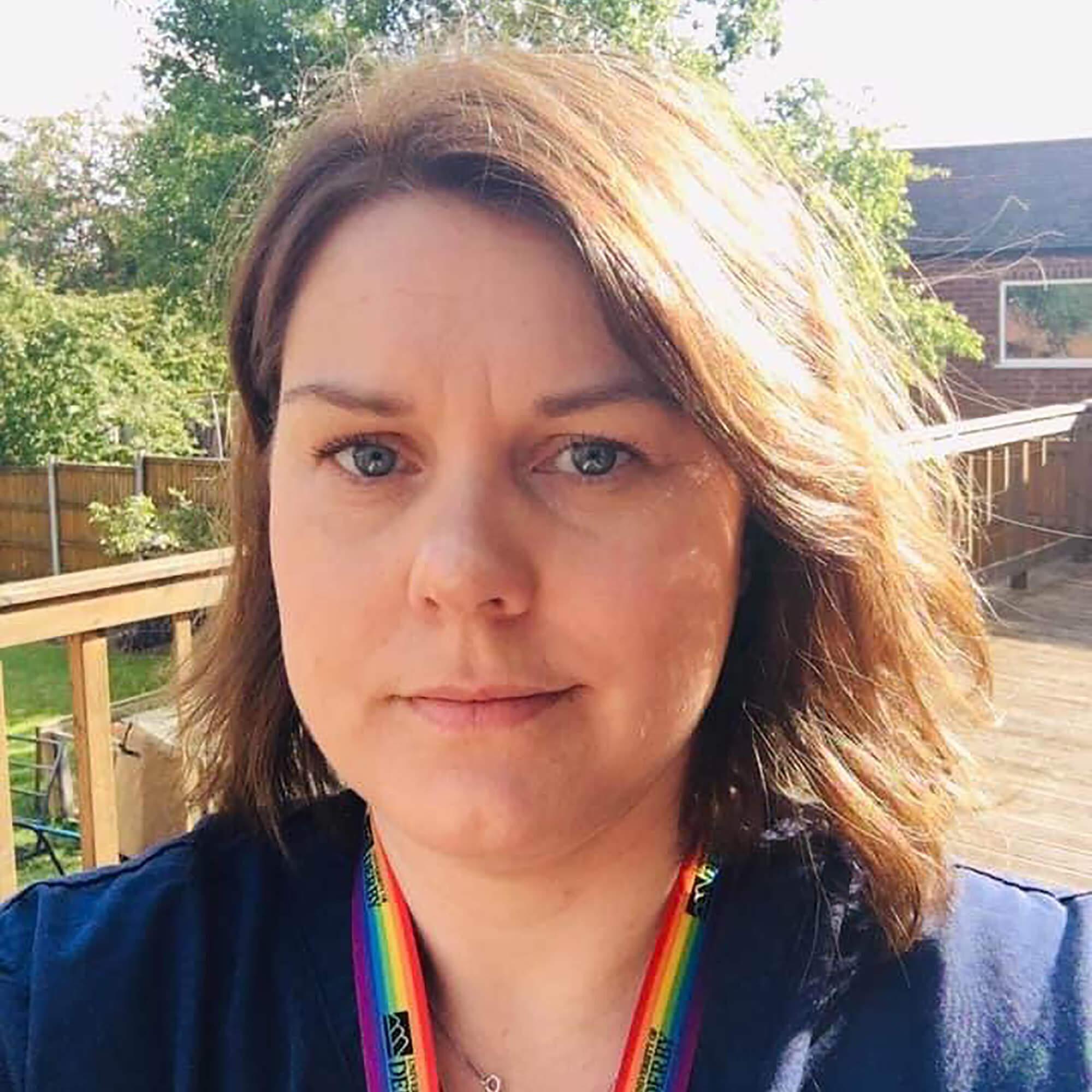 Louisa standing outside in a garden wearing a University of Derby lanyard