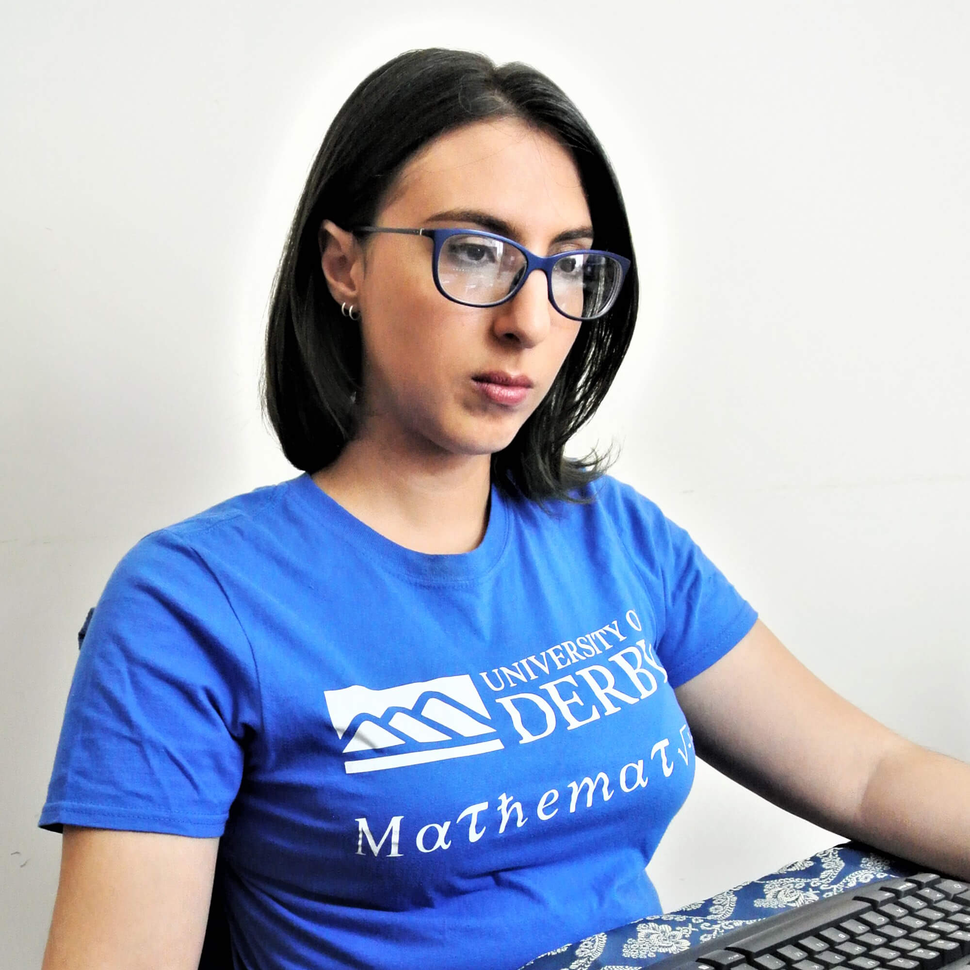 Lucia sitting at a computer wearing a University of Derby Mathematics t-shirt