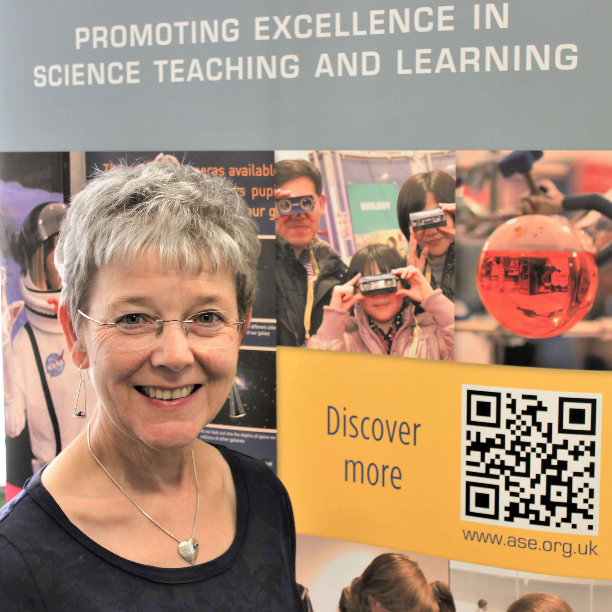 Maria Dent standing in front of a stand at an ASE conference