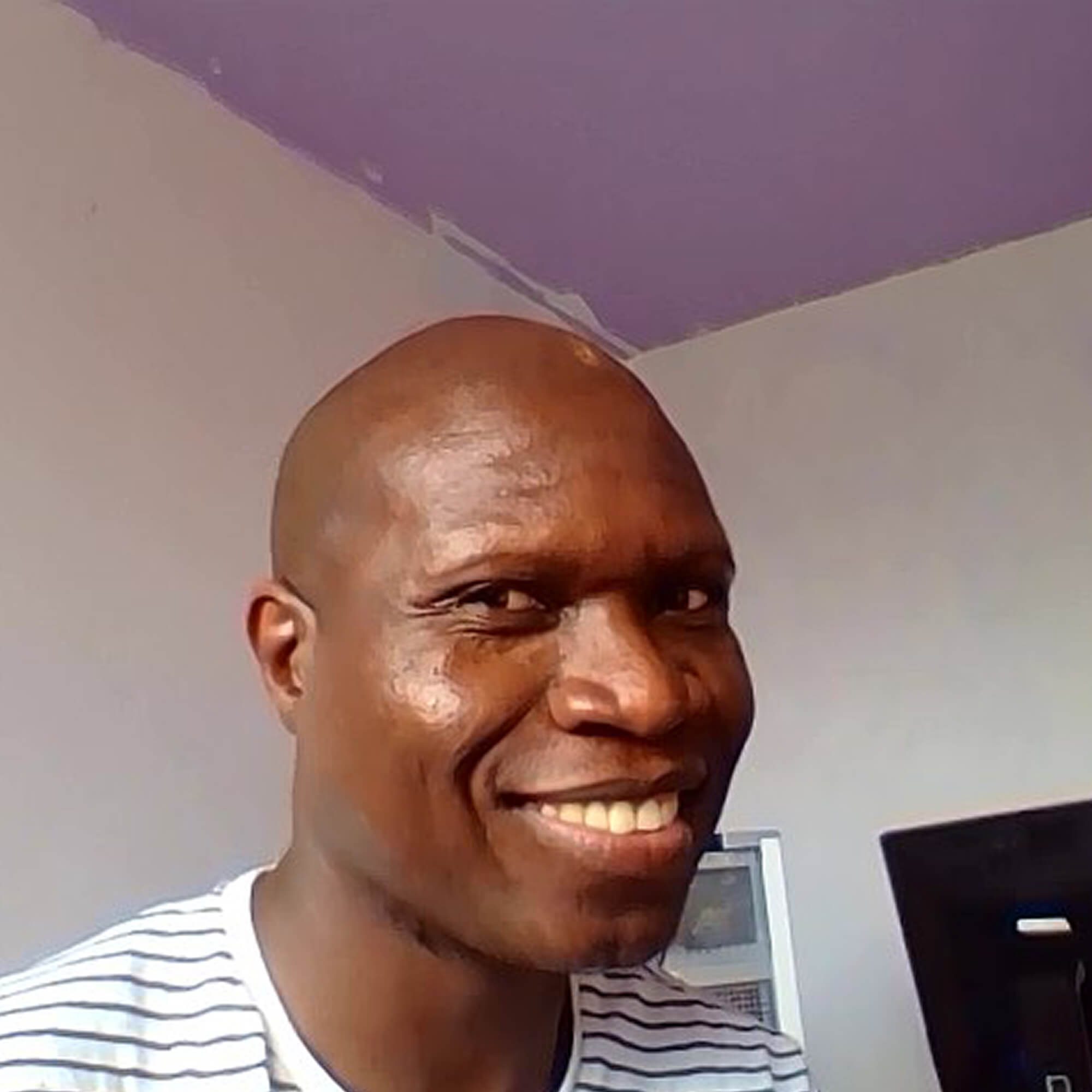 Mthulisi smiling next to a laptop